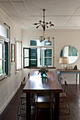Dark wooden dining table, wooden floor and blue shutters in vintage-style interior