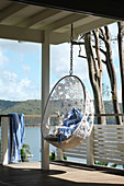 Hanging chair made from white crocheted lace on roofed veranda