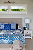 Blue-and-white patchwork quilt and scatter cushions on bed with upholstered headboard