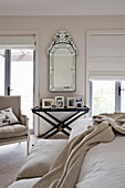 Mirror on wall and pictures on black tray table in beige bedroom