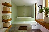Minimalistisches Badezimmer mit stufenförmiger Anordung von Dusche und Badewanne
