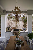 Decorative chandelier above wooden dining table on roofed terrace with pillars