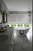 Twin sinks and modern, free-standing bathtub next to window in marble bathroom