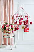 Bouquet of flowers on a chair behind it DIY advent calendar in white, red and pink