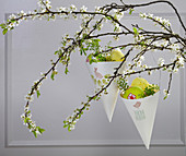 Handmade Easter decorations hung from branch of cherry blossom