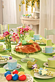 Easter nest made from sweet bread wreath on Easter table decorated in blue and green