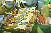 Paper napkins with egg cups used as napkin rings, paper bunny name cards and freesias