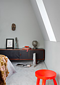 Orange stool and low sideboard in bedroom with slightly sloping wall