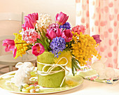 Spring arrangement of tulips, hyacinths and mimosa in vase with felt cover