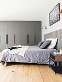 Doppelbett und grauer Einbauschrank im Schlafzimmer