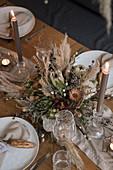 Gesteck aus Trockenblumen auf gedecktem Hochzeitstisch
