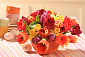 Arrangement of spring flowers in shades of red in bowl
