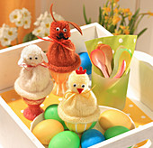 Knitted egg warmers with pompoms decorated as rabbit, lamb and chick