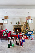 Christmas tree and blue and red furnishings in front of open fireplace