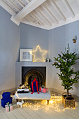 Christmas decorations and gifts in front of corner fireplace in room with pale blue walls