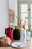 Branches in modern vase and insulated jugs in rustic kitchen
