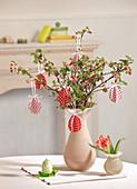 DIY-Ostereier aus rot-weiß gepunktetem Papier hängen an blühende Zweigen