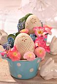 Eier mit dekorativem Lochmuster, Bellis, Traubenhyazinthe und Primel