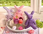 Handmade cloth rabbits in Easter nest with eggs and vase of ranunculus