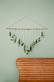 Handmade wall hanging: bunches of herbs hanging from bamboo cane