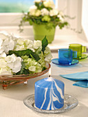 Blau-weiß marmorierte Kerze auf dem Tisch mit weißen Hortensien