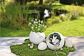 Osterdeko mit Vase und Nest aus Pappmache auf Moos