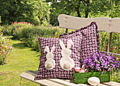 Purple cushion with appliqué rabbits on garden bench