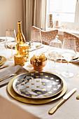 Festlich gedeckter Tisch in Gold und Weiß mit Portrait-Tellern