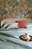 Goldener Teller und Tasse auf dem Bett vor exotisch gemusterter Tapete