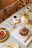 Coffee and cake on festively set table in gold and white