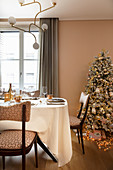 Festlich gedeckter Tisch im Esszimmer in Rosé mit Weihnachtsbaum