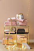 Towels and wrapped gifts on golden shelves