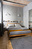 Bed in bedroom in shades of grey with vaulted ceiling
