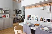 Multifunktionaler Wohnraum in einer Einzimmerwohnung in Grautönen