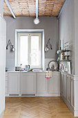Open-plan kitchen in shades of grey with panelled cabinets and vaulted ceiling