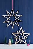 Selbstgemachte Sterne aus Holzspateln an blauer Bretterwand
