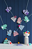Garland of paper gloves and hats with pompoms