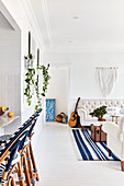 Barstools in open-plan interior with white floor and blue accents