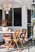 Rattan folding chairs around pink pedestal table on terrace