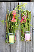 Candle lanterns made from knotweed, preserving jars and flowers hung on wooden fence