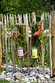 Candle lanterns made from knotweed, preserving jars and flowers hung on paling fence