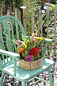 Arrangement of knotweed, snapdragons and zinnias in basket