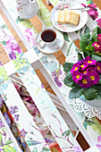 Primulas, tea and cake on DIY palette table decorated with springlike floral pattern