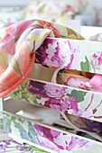 Wooden crate decorated with floral wallpaper remnants