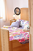 Floral bed linens on wooden bed