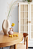 Grasses and fruits in vases on round table in dining room
