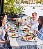 Freunde am gedeckter Tisch mit sommerlichen Vorspeisen auf Terrasse