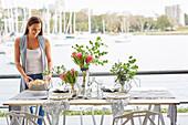 Sommerlich gedeckter Tisch mit Blumen, Frau mit Brotkorb