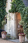 Arched porch doorway surrounded by ivy and flanked by potted plants with firewood stacked in porch
