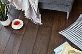 Teacup, blanket, cushion and magazines on dark wooden floor